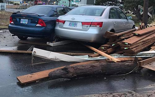 big waves and logs tossed onto a parking lot in Rockaway Beach squish cars together